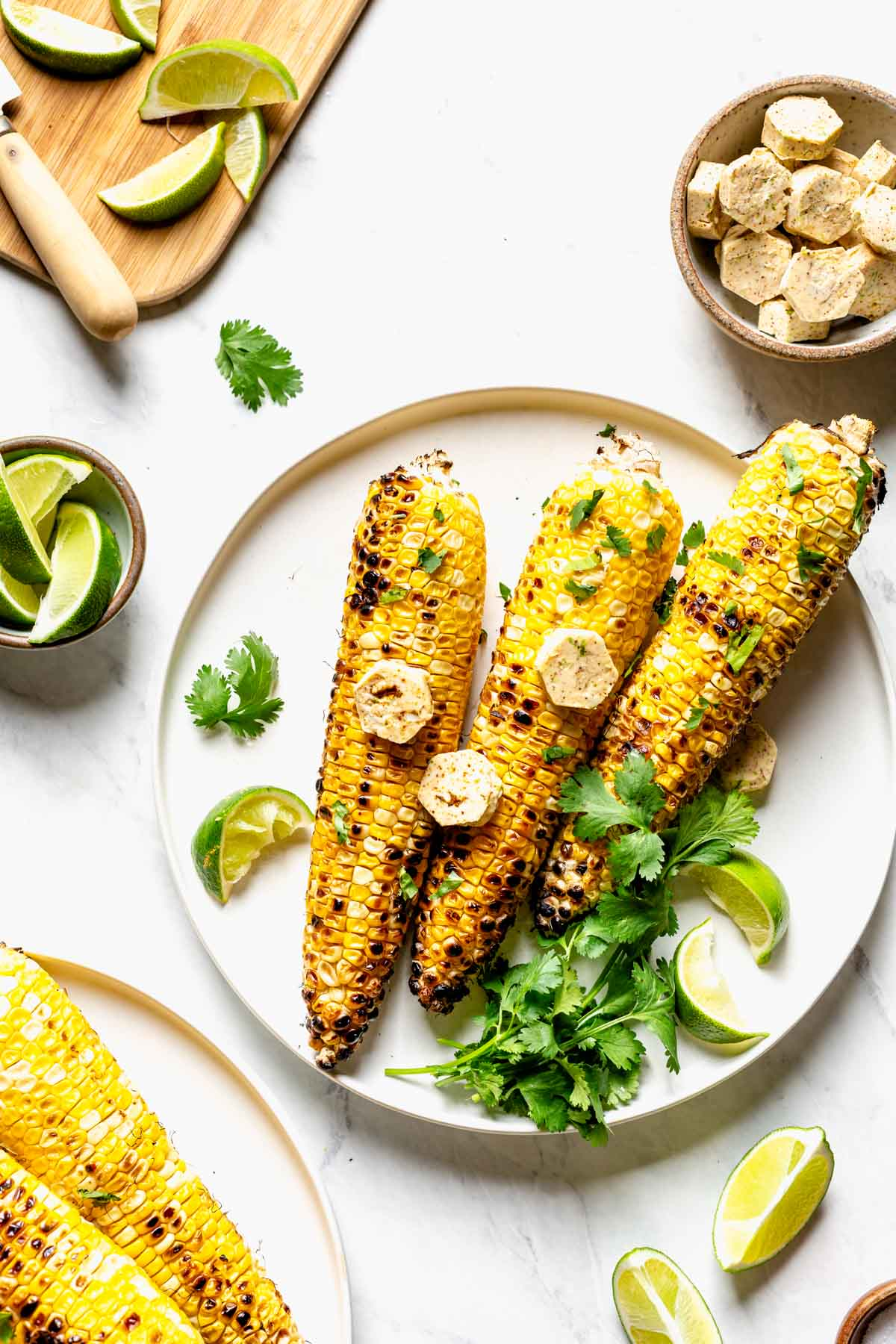 a plate of corn on the cob with cilantro and lime wedges