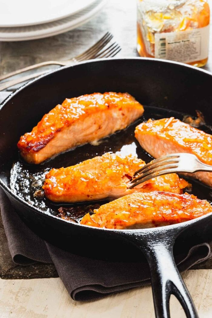 a cast iron skillet with four pieces of salmon, a fork is flaking one of the pieces