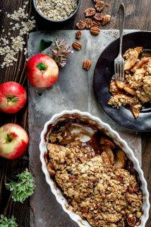 a dish of apple crisp and a serving on a black plate