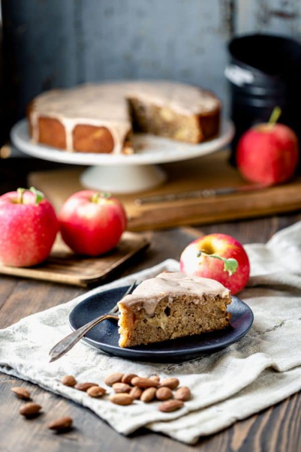 a slice of apple cake and a cake on a cake stand with apples in front