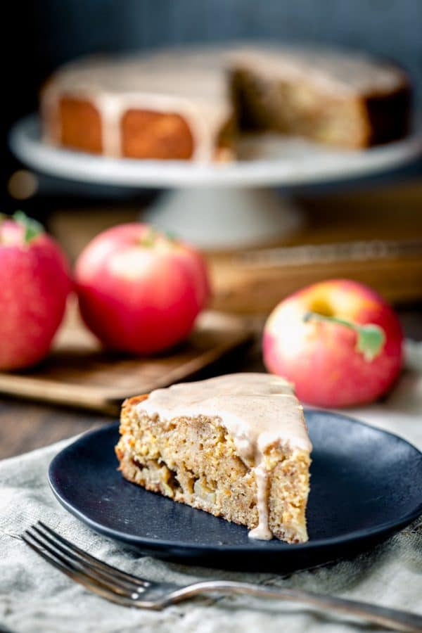 Apple cake slice with maple icing drizzling down the side