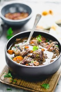 a close up from 3/4 side angle of a black bowl with beef burgundy
