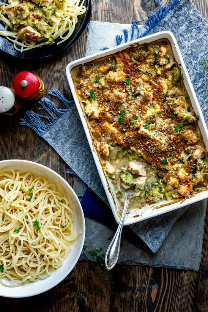 overhead tablescape with a casserole of chicken divan, and a bowl of pasta