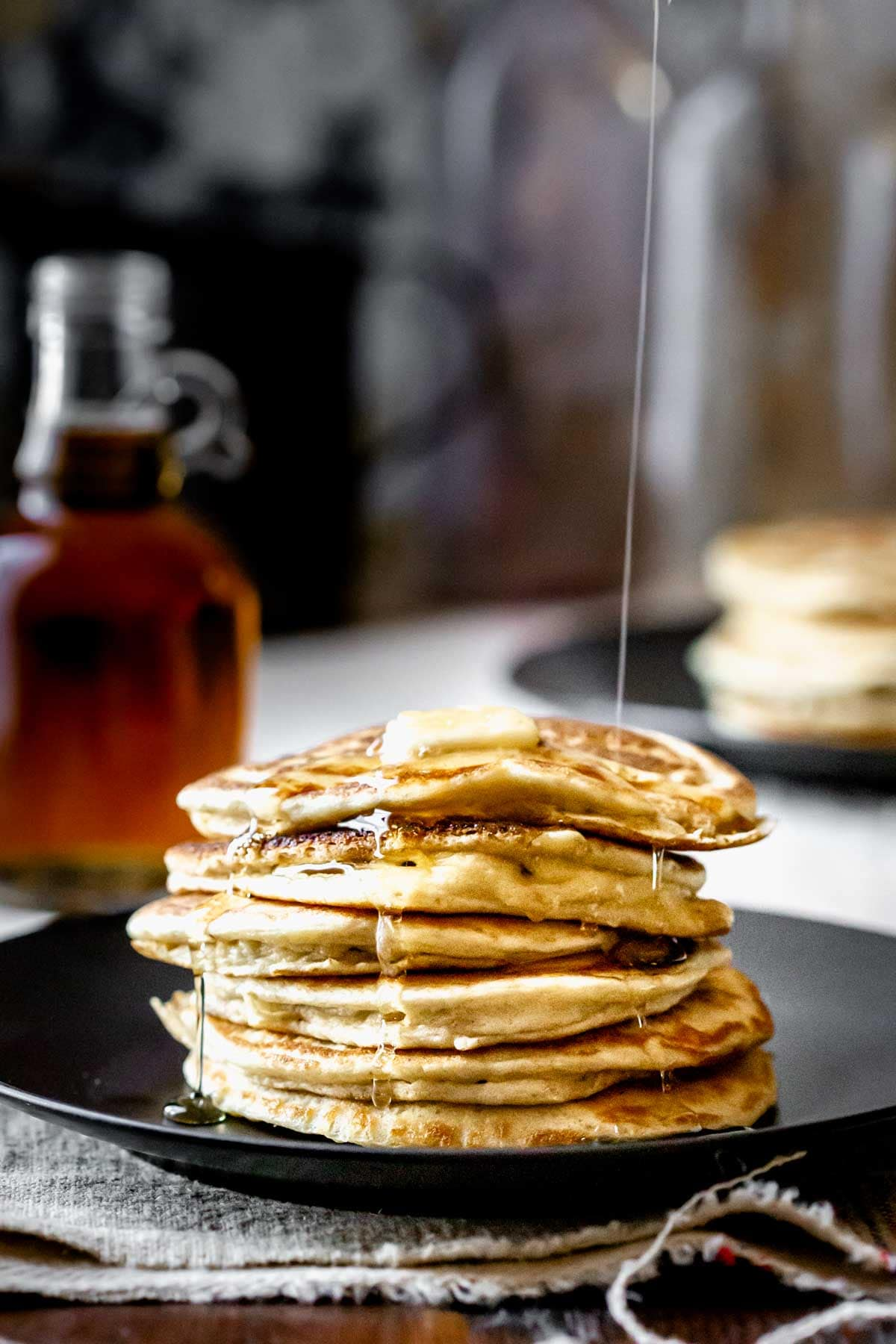 a stack of pancakes with maple syrup running over it