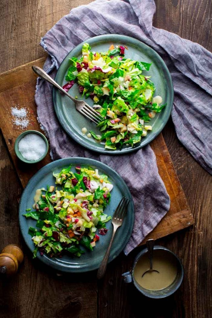 OVerhead two plates of chopped salad with purple linen