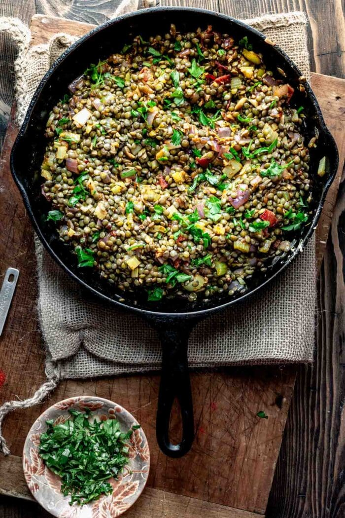 a skillet with lentils with parsley on top