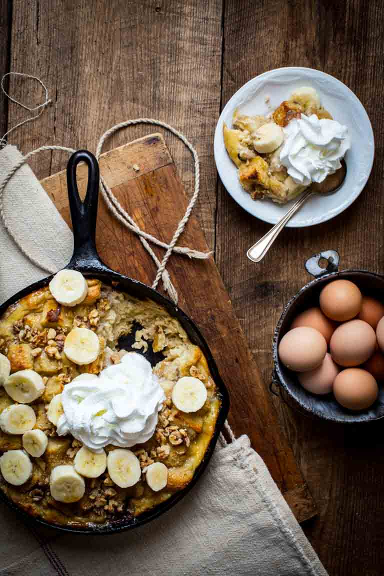 banana bread pudding in skillet next to bowl of eggs