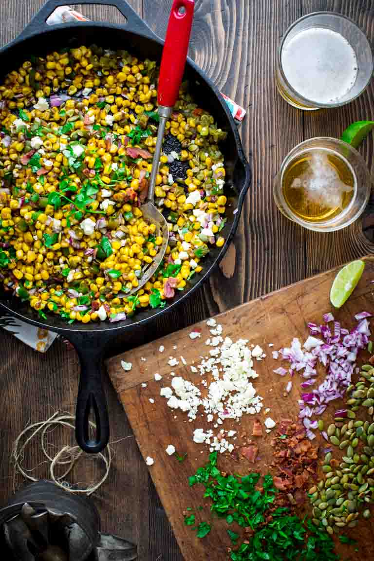 This Loaded Mexican Street Corn Sauté is an easy skillet side dish variation of Mexican street corn made with frozen corn and topped with flavorful additions like pepitas, Cotija cheese, bacon, pickled jalapenos and cilantro and is ready in less than 10 minutes. Healthy Seasonal Recipes | Katie Webster