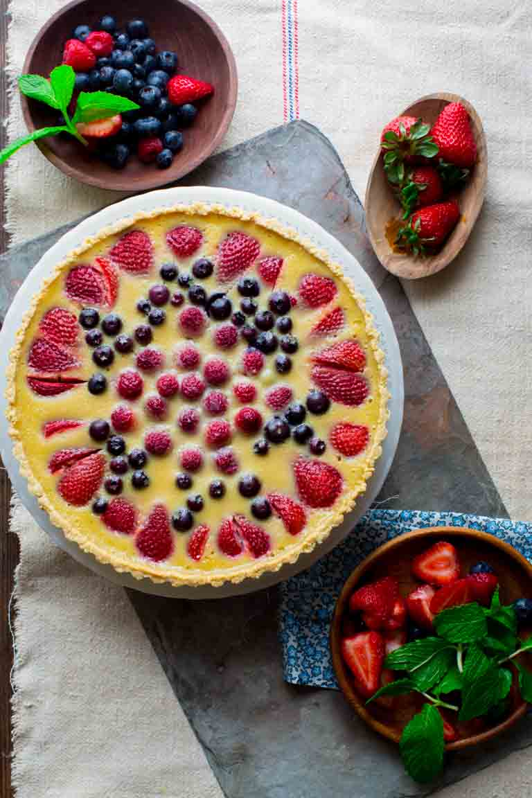 Celebrate the best of what Summer has to offer with this Red White and Blue Buttermilk Berry Tart! A lightly sweetened buttermilk custard is poured over a mix of fresh, plump and delicious summer berries and baked in an easy press-in crust and then topped with a dollop of whipped cream. The perfect warm weather dessert! | Healthy Seasonal Recipes | Katie Webster