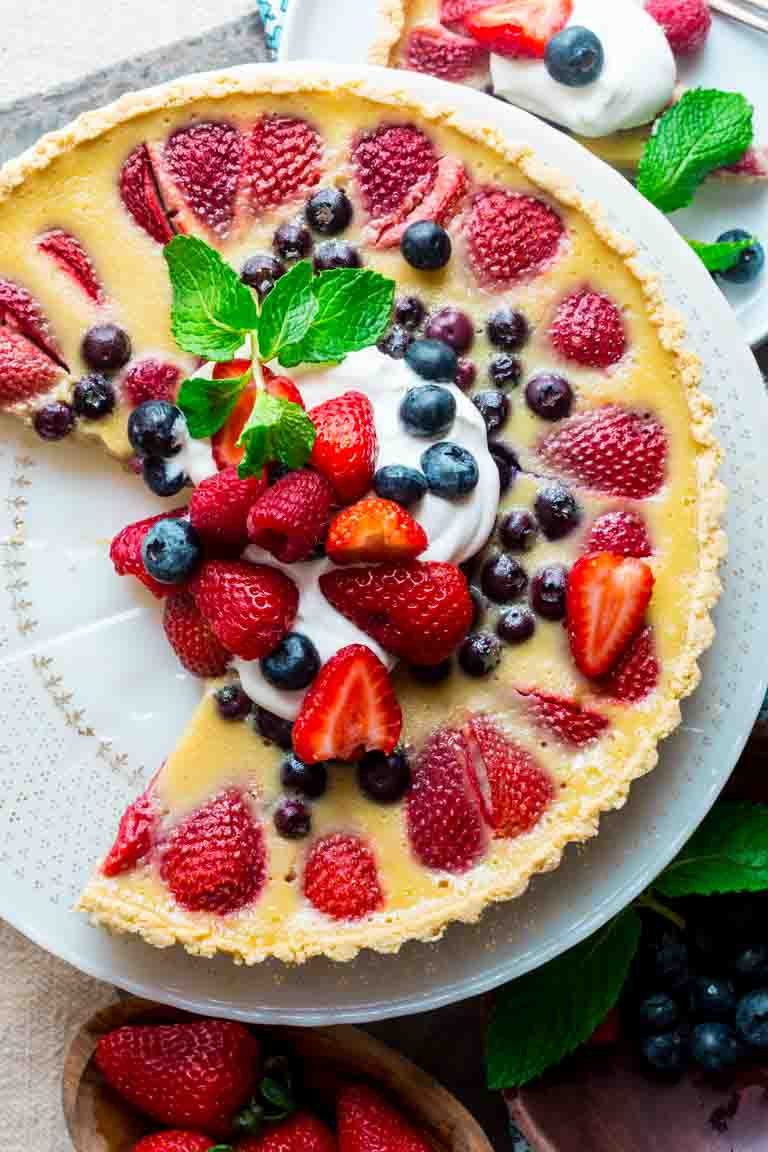 Celebrate the best of what Summer has to offer with this Red White and Blue Buttermilk Berry Tart! A lightly sweetened buttermilk custard is poured over a mix of fresh, plump and delicious summer berries andbaked in an easy press-in crust and then topped with a dollop of whipped cream. The perfect warm weather dessert! | Healthy Seasonal Recipes | Katie Webster
