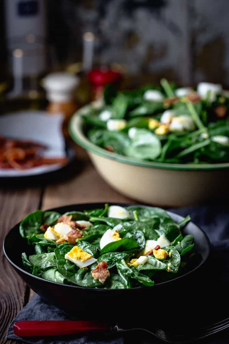 A serving of spinach salad with bacon and eggs