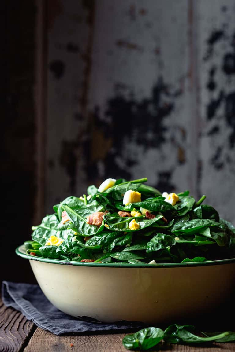 Side view of a table with a large bowl of spinach salad with Bacon and Eggs