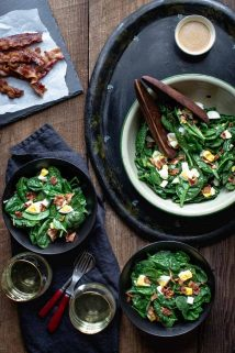 Overhead view of a table with three bowls of spinach salad with Bacon and Eggs
