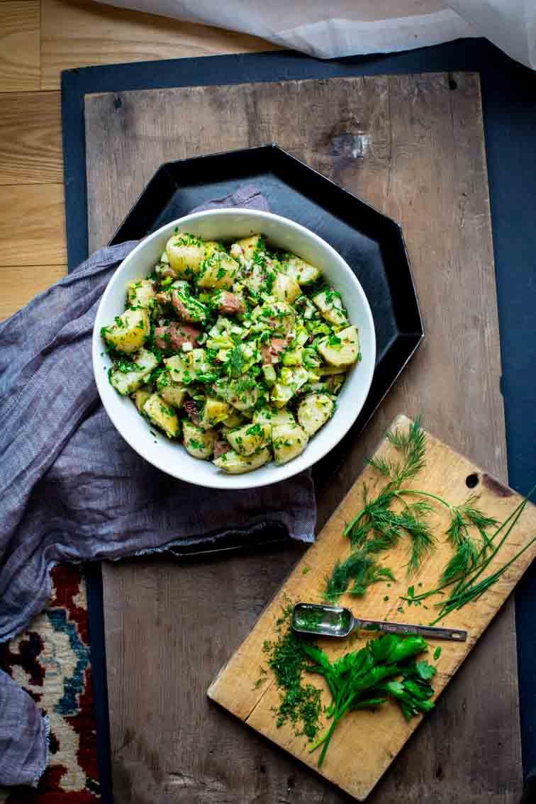 vegan potato salad in large bowl next to cutting board