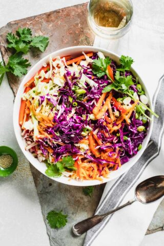 Close-up of coleslaw in a bowl from overhead. Garnished with cilantro.