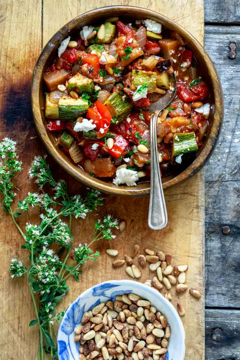 a bowl of ratatouille with goat cheese and pinenuts