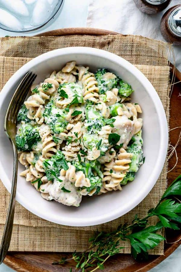 A close up of a pale pink bowl with spiral pasta and chicken alfredo with broccoli