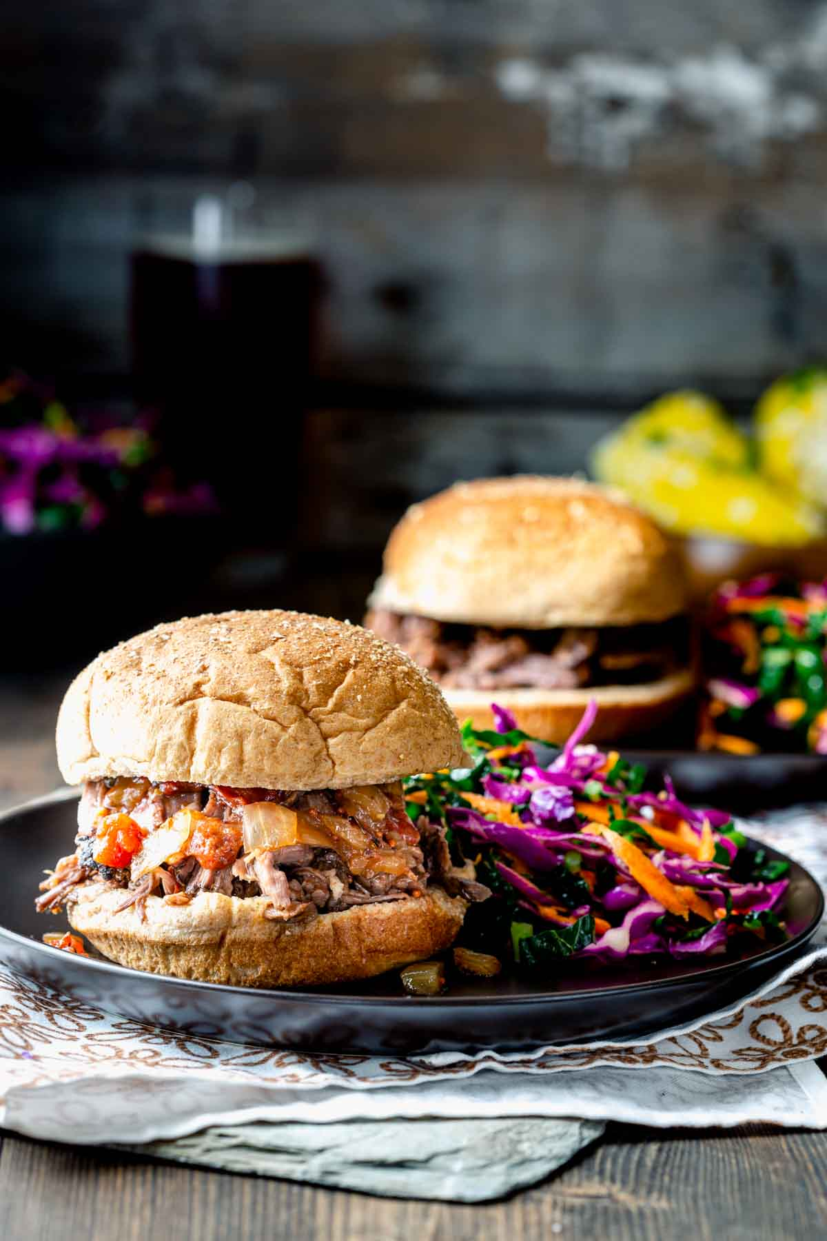 two plates with pulled beef sandwiches and coleslaw