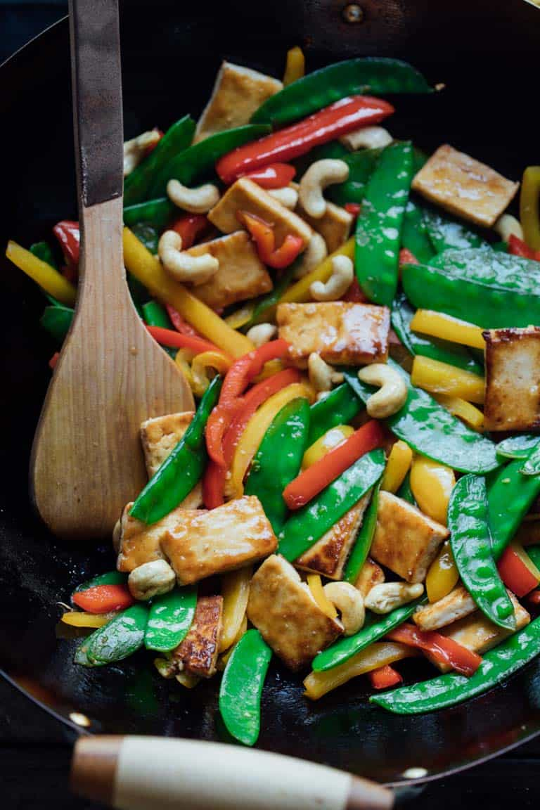 veggie stir fry with tofu and cashews in a wok