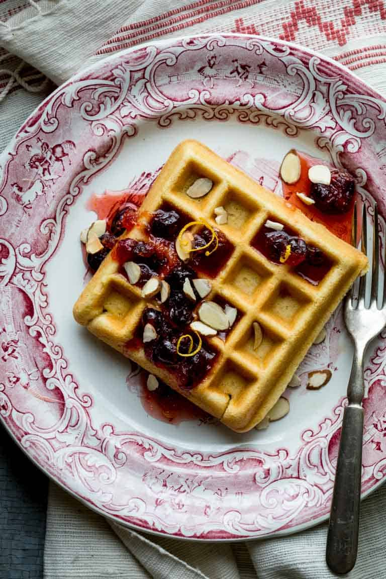 On Christmas Morning, wake up to these Almond Waffles with Cranberry Orange Honey Syrup. The whole family will love them. You can make the honey syrup ahead and do some of the prep ahead so they are easy to make. | Healthy Seasonal Recipes #breakfast #Christmasbreakfast