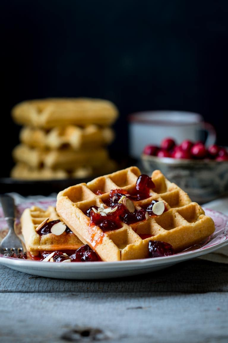 On Christmas Morning, wake up to these Almond Waffles with Cranberry Orange Honey Syrup. The whole family will love them. You can make the honey syrup ahead and do some of the prep ahead so they are easy to make. | Healthy Seasonal Recipes #breakfast #Christmasbreakfast #cranberry #healthy #morning