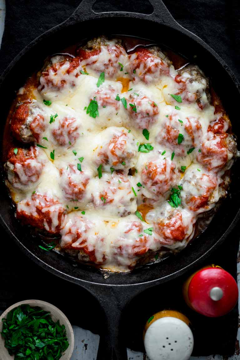 Healthier Baked Meatball Parmesan made with grass-fed beef and bulgar wheat. Baking the meatballs on a rack helps prevent them from becoming greasy. HealthySeasonalRecipes.com #grassfedbeef #meatballparm #italianfood #comfortfood #healthyrecipe