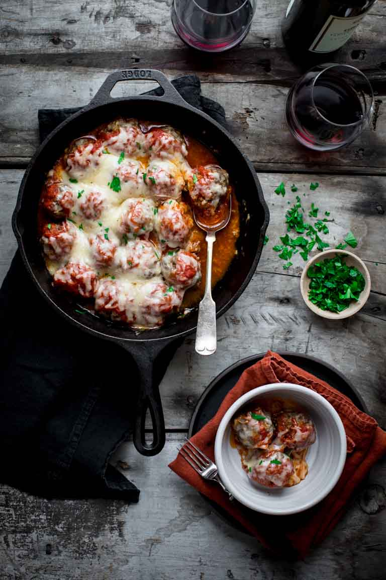 oven baked meatballs in a cast iron skillet next to a bowl