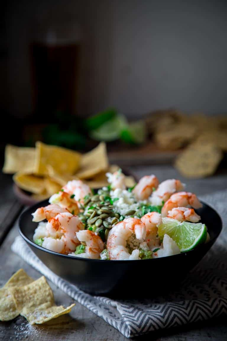 Fancy Guacamole Shrimp Cocktail- Facncy up classic guac by topping it with Cotija Cheese, Pepitas and cooked shrump for a grain-free and super festive party appetizer for the superbowl or cinco de mayo