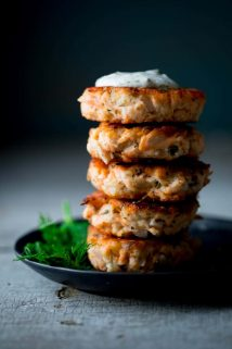 A stack of Lemon Caper Salmon Cakes on a black plate with a sprig of dill