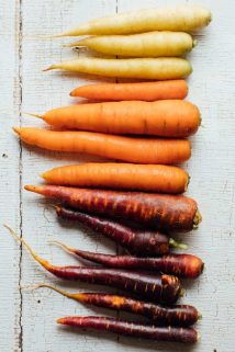 all different colored carrots lined up on a white surface