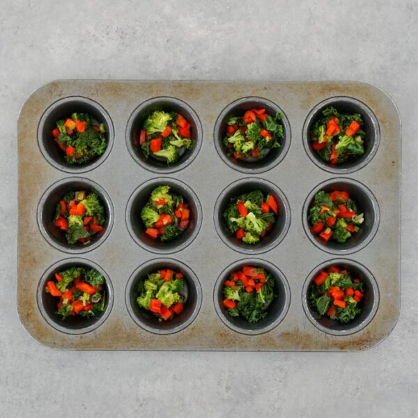 divide the veggies among the wells of the muffin tin