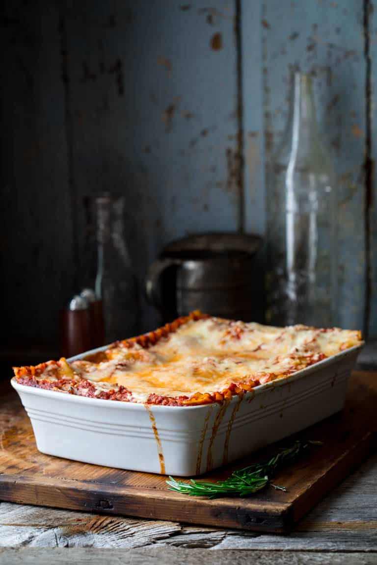 Vegetarian Caramelized Onion and Portabella Mushroom Lasagna in baking dish on a cutting board