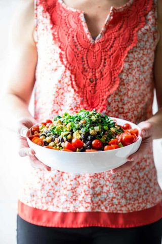 a woman's torso with a red shirt, hands holding a white bowl with a colorful bean salad with cherry tomatoes and cilantro