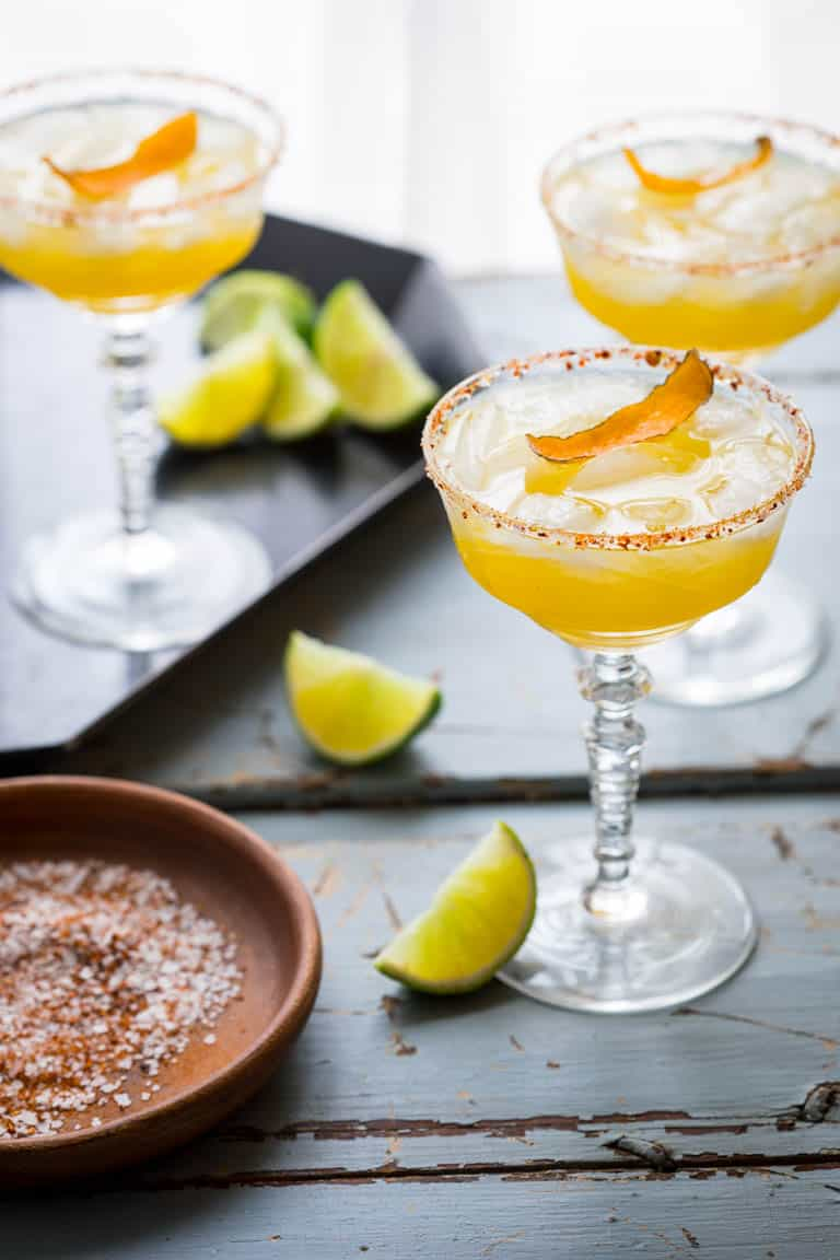 These smoky, tart and sweet Mescal Margaritas, made with Cuantro, freshly squeezed lime and orange juice have a salted rim with a surprising ingredient! #mescal #margarita #smoky #summer #cocktail #lime #orange