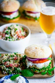 Burgers made from ground chicken, seasoned with za'atar and topped with cucumber mint tzatziki, lettuce and tomato! Get those grills fired up my friends! They're a middle-eastern flavored burger mash-up you won't want to miss. Healthy Seasonal Recipes by Katie Webster | #burger #tzatziki #chicken #cucumber #mint #zaatar #grill