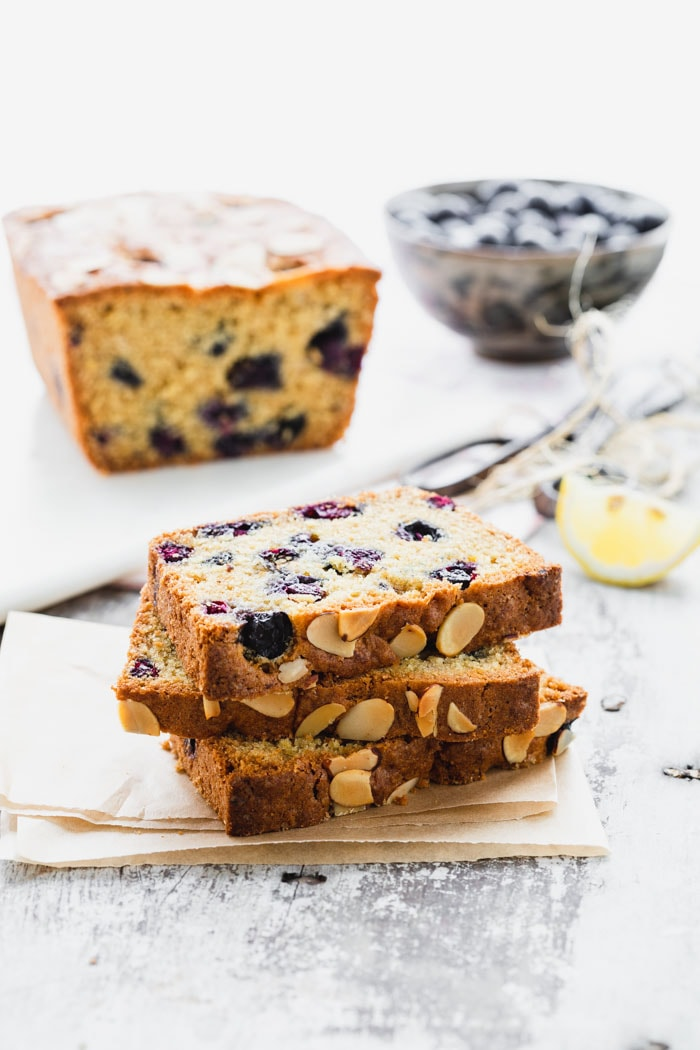 A stack of slices of blueberry bread next to a loaf and a bowl of blueberries