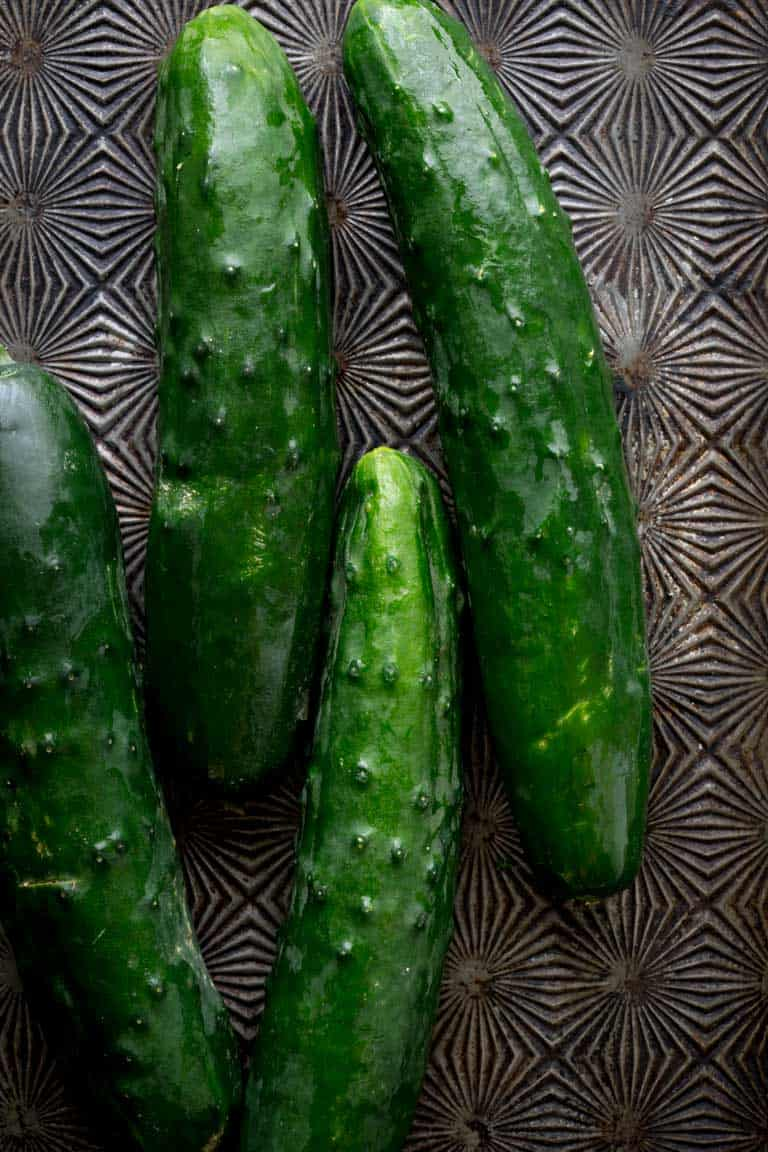 Have you ever wondered about why your cucumbers are bitter? Or whether or not you can freeze cucumbers? And what about how to grow cucumbers? Look no further than this Ultimate Guide to Cucumbers. These crunchy, refreshing veg is popular for good reason. See your questions answered below, along with cucumber recipes for inspiration. Healthy Seasonal Recipes by Katie Webster | #cucumber #summer #produce #fresh #gardening #cooking