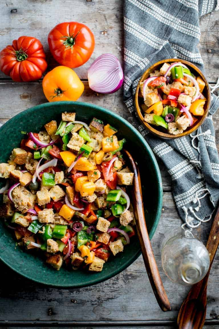 This rainbow panzanella has several fresh, colorful vegetables tossed in. It has a crust and softness that gets better as it sits. Perfect for summer potlucks and events! Healthy Seasonal Recipes by Katie Webster | #summer #vegetables #fresh #potluck #color #rainbow