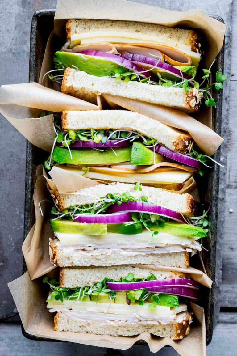 a pan stacked with turkey avocado sandwich halves