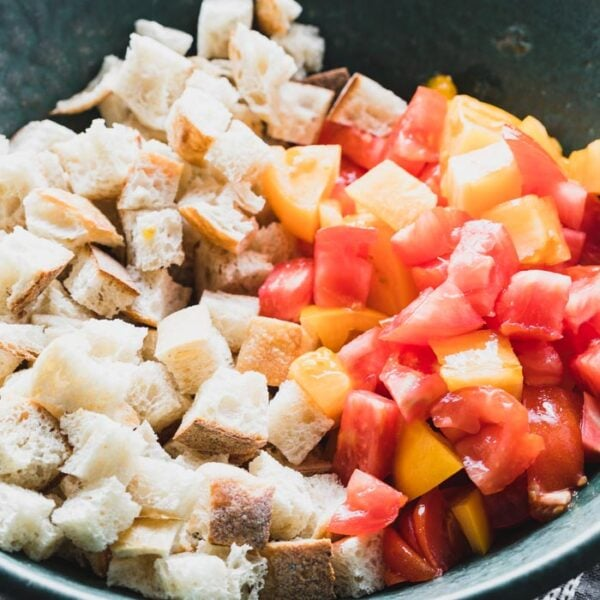 Add toasted bread and chopped tomatoes to the dressing.