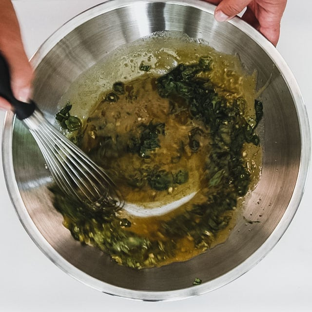 Whisk the dressing and basil in a large bowl.