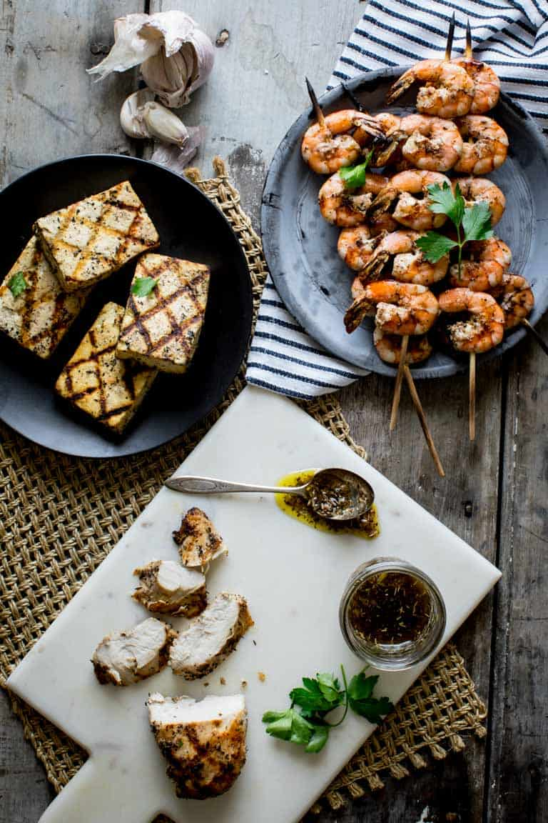garlic marinated grilled shrimp kebabs, marinated tofu, garlic marinated chicken seen overhead on a gray table with a jar of garlic marinade