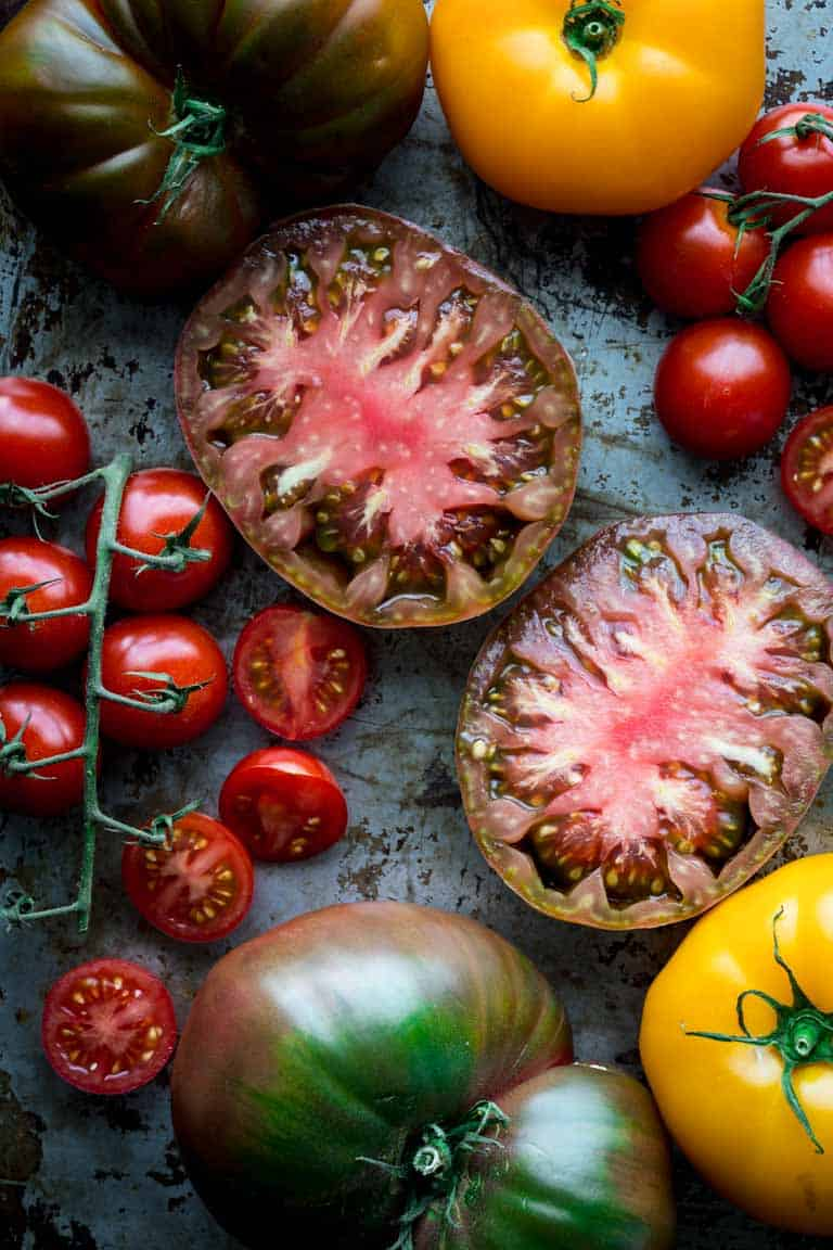 What makes tomatoes split? Should they be refrigerated? Can they help heal sunburns? Answers to these questions and many more are found in this Ultimate Guide to Tomatoes. Read on for the scoop about growing tomatoes, preparing them and what nutrients they bring to the table. Check out the several tomato recipes as well. Healthy Seasonal Recipes by Katie Webster | #tomatoes #producespotlight #guidetotomatoes