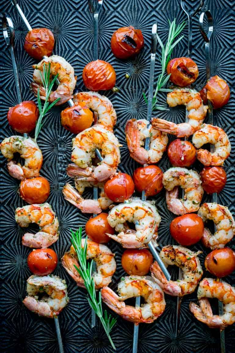 a black tray of shrimp kebabs with cherry tomatoes and rosemary