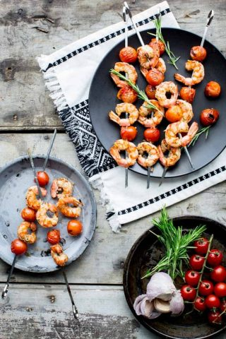 shrimp kebabs on a black plate on a gray table