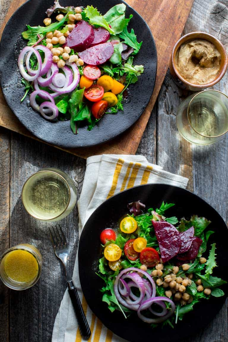 Two colorful salads with two glasses of white wine, a crock of german mustard and a jar of mustard salad dressing on a gray farm table