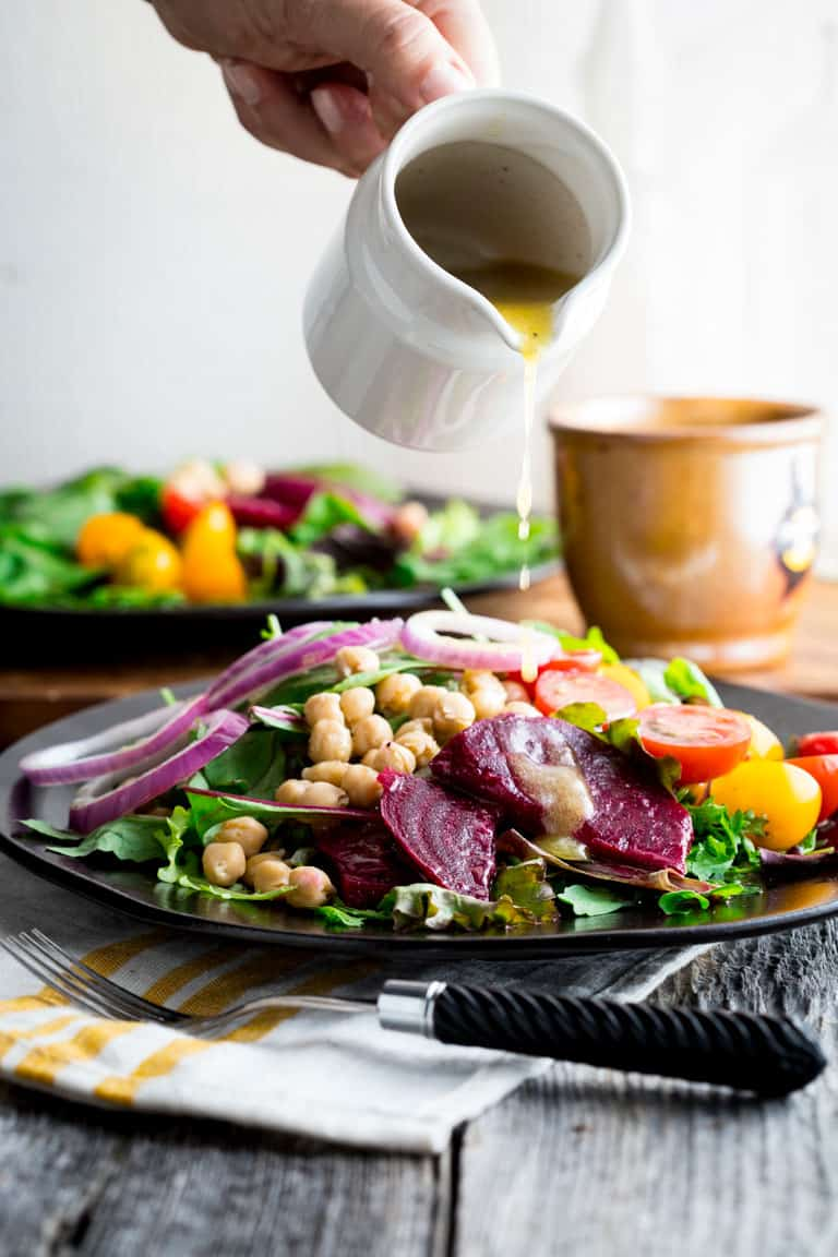 a white pitcher pouring dressing over a salad with beets and onions