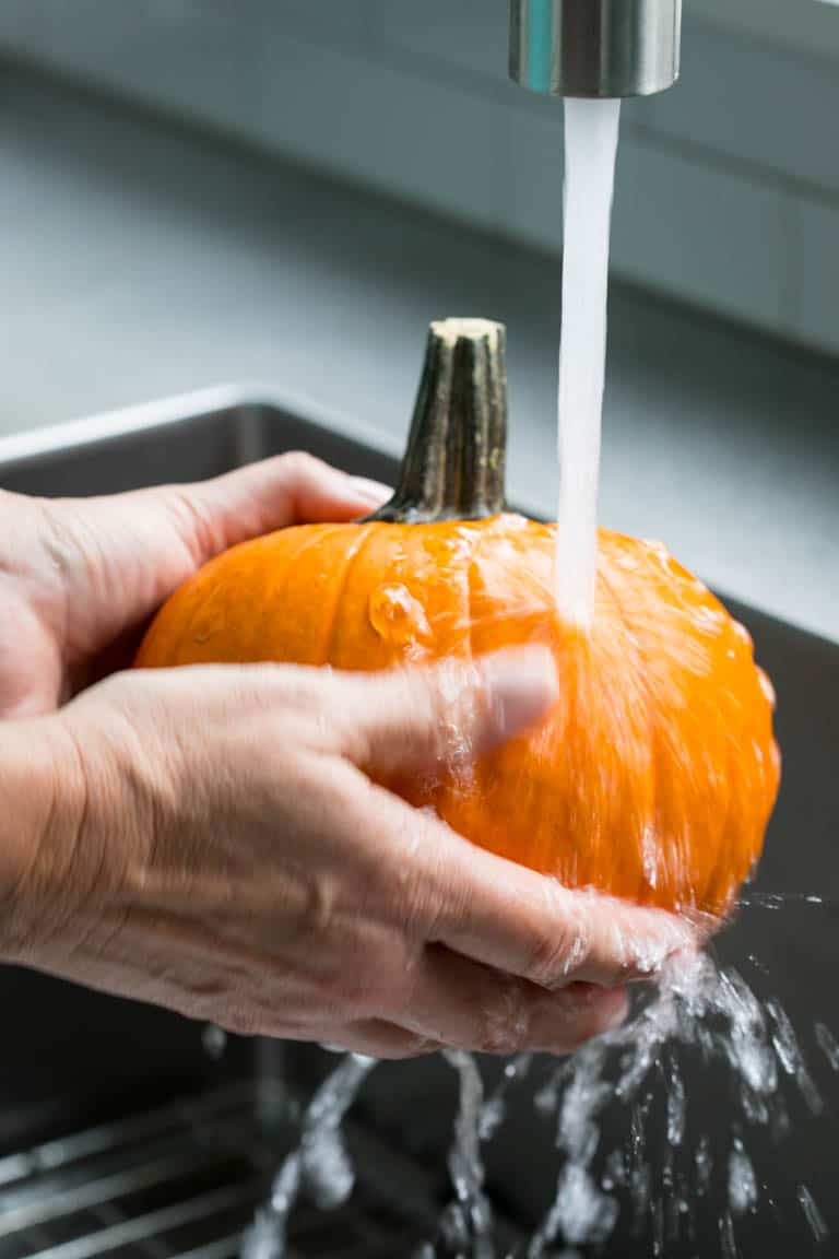 Wash your fresh cooking pumpkin before you peel, seed and cut it.