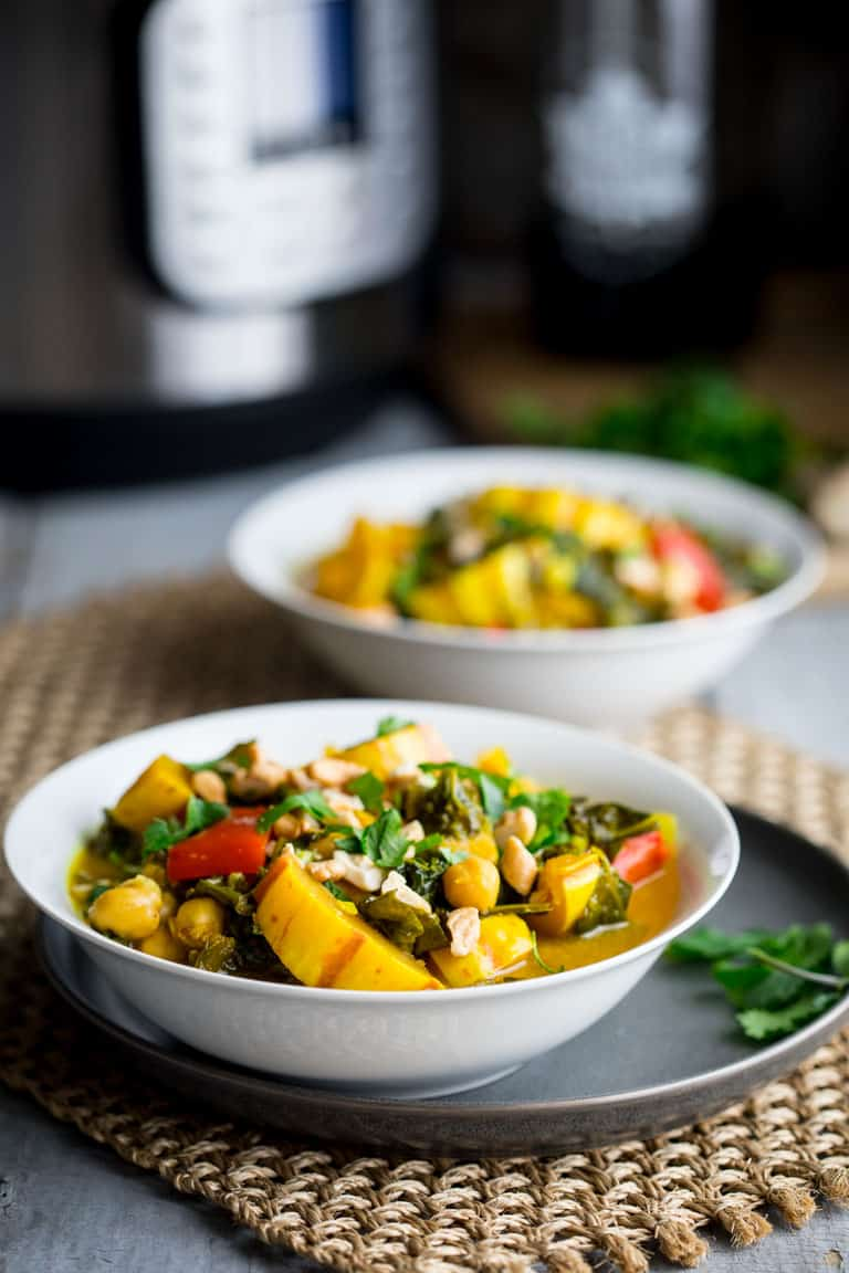 A view from the side of two white bowls on a woven mat with veggie curry in them, an instant pot is behind them