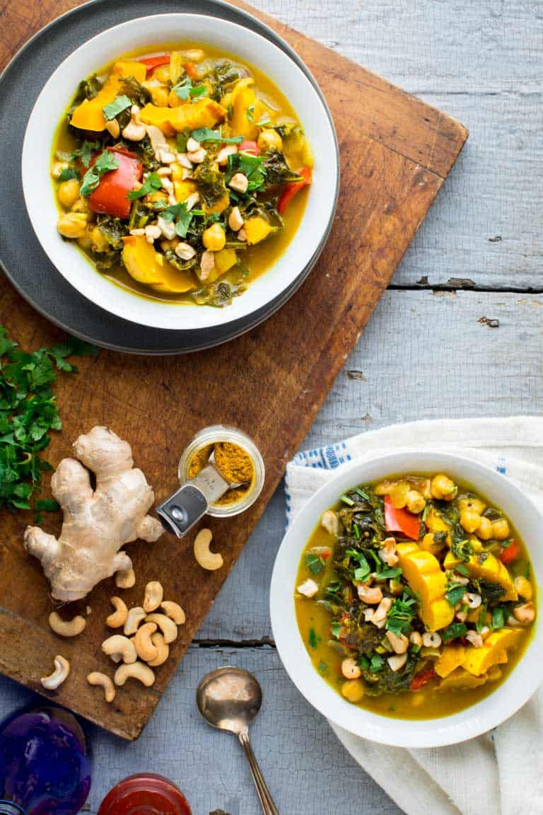 Instant Pot Veggie Curry in two bowls overhead with a cutting board with ginger, curry, cashews and cilantro on it.